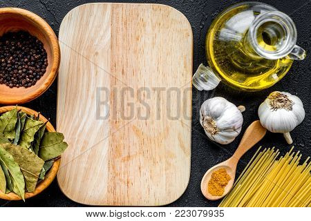 In restaurant. Mock up for menu or recipe. Wooden cutting board near ingredients. Raw pasta, oil, garlic, spices on black background top view.