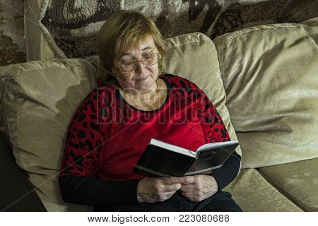 A woman is reading a book sitting on the couch. Evening. With a table lamp.