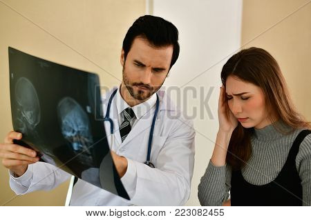 Health Concepts. Doctor and patient viewing x-ray film. The doctor and the patient feel relaxed at the check-in time. The doctor encouraged the patient. Inside the hospital are doctor X-ray patient.