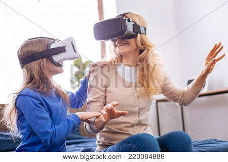 Entertainment. Cheerful fair-haired young mother and daughter wearing VR headset and entertaining while sitting on the bed