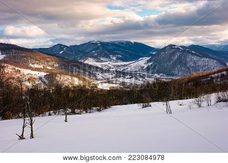 beautiful mountainous countryside in afternoon. gorgeous winter landscape with cloudy sky and snowy slopes