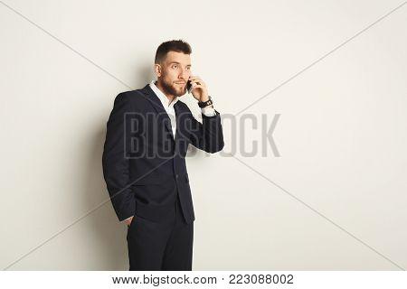 Handsome young caucasian businessman posing in studio and talking on mobile on white background. Confident serious man in formal clothes, copy space