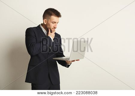 Handsome young caucasian businessman posing in studio and using laptop, typing, surfing the internet on white background. Confident serious man in formal clothes, copy space