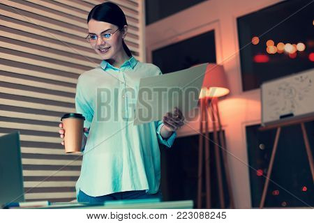 Professional analyst. Charming dark-haired woman standing near her work desk, holding a cup of coffee and a printout with bar graph while looking at the laptop screen