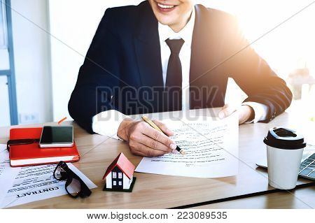 agreement paper,estate agent gives pen and documents agreement with customer to sign contract for . Concept insureance