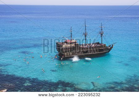 Tourists are swimming in the sea near the pirate ship