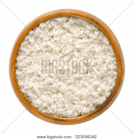Atlantic sea salt in wooden bowl. Unrefined, unwashed, untreated, coarse salt without additives. Harvested from clay layer. Isolated macro food photo close up from above on white background.