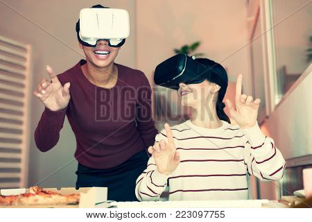 Best game. Two upbeat female friends wearing VR headsets and laughing while having fun during the home party