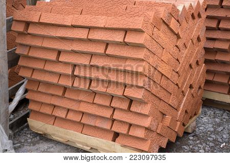 Red clay building bricks stacked on pallets still wrapped in their plastic for delivery at a warehouse, factory or construction site.