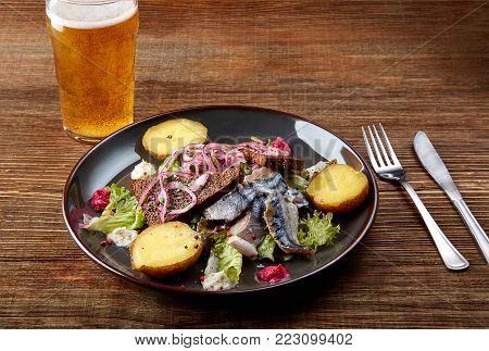 Grilled mackerel fish with baked potatoes and glass of beer on wooden table. Photo for the menu. Still life. Copy space. Flat lay