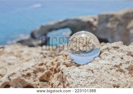 Glass ball near Monachus Monachus Arch. Cavo greco cape. Ayia napa, Cyprus. Mediterranean sea landscape