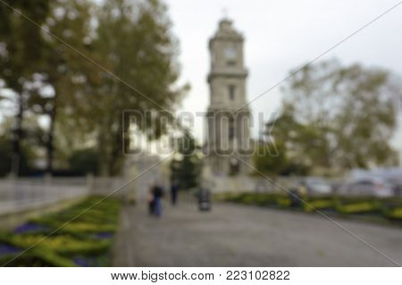 blurred unfocused background with clock Tower in the park close to the entrance gate of Dolmabahce Palace, Istanbul, Turkey. Natural bokeh.