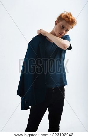 Putting on. Handsome unsmiling red-haired young man putting a jacket on and staring and having a modern haircut