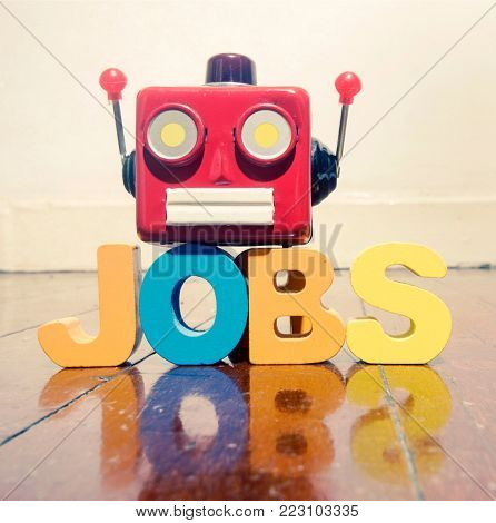 red retro robot head on the word  JOBS  on old wooden floor with reflection