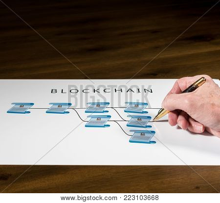 Blockchain schematic on printout on desk with senior technology executive pointing at one of the encrypted blocks of blockchain poster