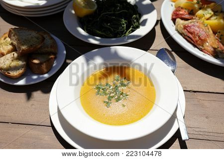 Fish soup dish from red scorpionfish next to boiled scorpionfish, bread, greens salad on wooden table in the greek tavern, healthy seafood lunch concept. Horizontal. Close-up. From above. Daylight.