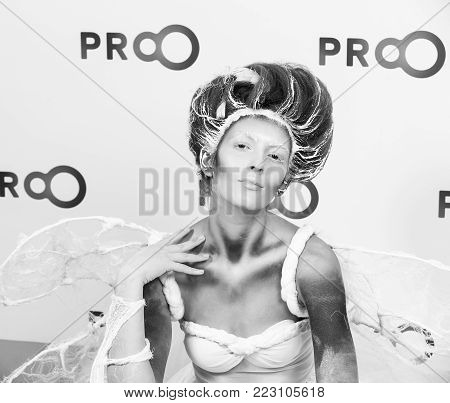 Kyiv, Ukraine - September 16, 2015: girl model with hair performs professional makeup and body art on masterclass at International exhibition of perfumery and cosmetics Intercharm as animal in white