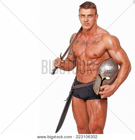 Hot topless man who is holding helmet and sword