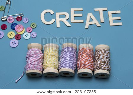 Arts and crafts image of colourful twine with buttons and safety pins