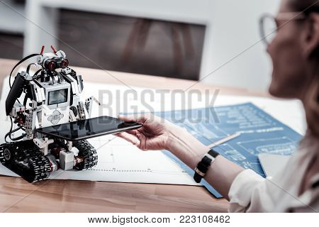 Keep it. Delighted office worker expressing positivity and sitting in semi position while taking gadget from robot