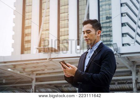 young smart asian business man wearing modern black suit with mobile smart phone in building city background, successful, internet network connection, technology communication, financial concept