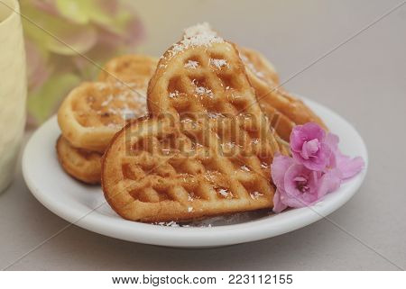 Waffle in Heart Shape in White Plate with little Pink Flowers.