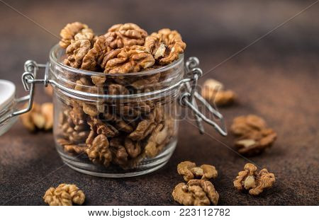 Walnuts. Walnut kernels and whole walnuts on rustic table.