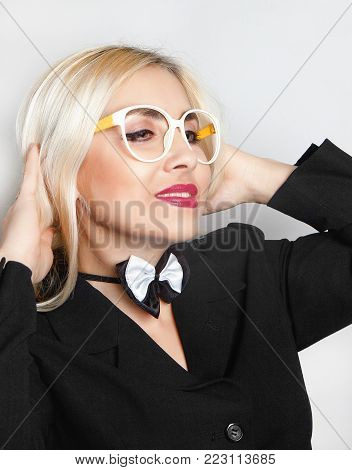 Funny blonde in a business suit with a bow tie on elastic band and glasses without glass.