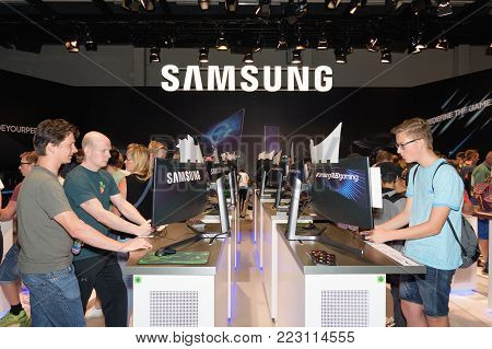Cologne, Germany - August 24, 2017: Trade fair visitors play and test computer games at the booth of the electronics company Samsung at Gamescom 2017. Gamescom is a trade fair for video games held annually at the Koelnmesse.
