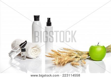 Spa cosmetics, jar of cream, oil with wheat, white cosmetic bottles with apple and wheat towel, candle, soap isolated on white. Without label. The concept for advertising cosmetics. Still life. Copy space