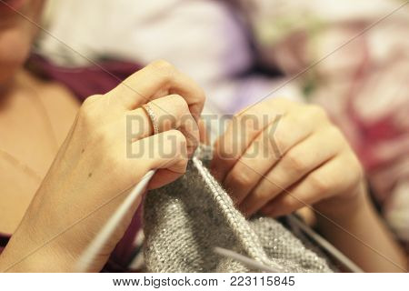 Woman knits with knitting needles gray sweater from natural woolen threads
