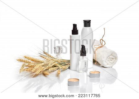 Herbal and mineral skincare. Jar of cream, oil with wheat, white cosmetic bottles. Without label. The concept for advertising cosmetics. Still life. Copy space