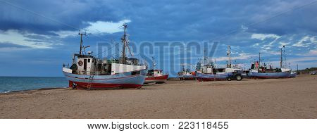 Evening scene at the Jammerbugten, Denmark. Blue hour. Fishing boats at Thorup Strand, Jylland. Cloudy summer evening in Denmark.