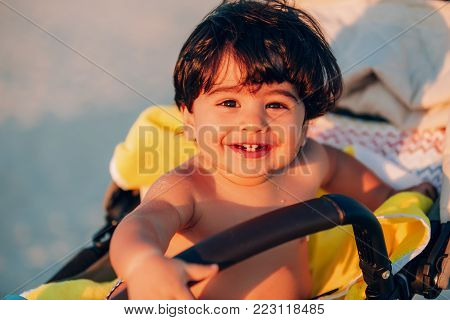 portrait of a beautiful baby boy playing on the shoreline