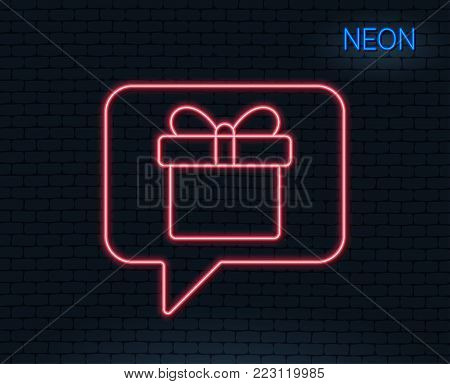 Neon light. Dreaming of Gift line icon. Present box sign. Birthday Shopping symbol. Package in Gift Wrap. Glowing graphic design. Brick wall. Vector