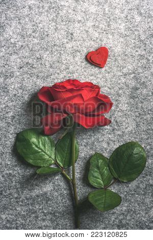 Single red rose and two red hearts - Retro style romantic image with a beautiful  red rose and two red fabric hearts over one another, on a vintage grey fabric background.