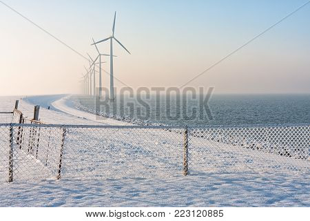Dutch dike in winter with snow, fence and long row of wind turbines offshore in the water disapearing in winter haze