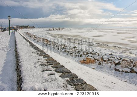 Winter landscape with snow and frozen sea near harbor and beach Urk, Dutch fishing village at the IJsselmeer
