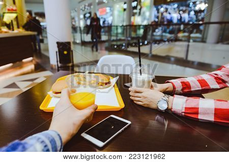 couple sit in cafe inside mall eat burgers and drink juce