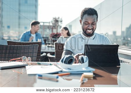 Education is so interesting. Happy African American guy grinning broadly while looking at a screen of his touchpad and working on a home assignment outdoors.