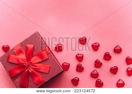 Red beautiful box with ribbon and bow on red background. Nearby are symbols in the form of a heart. Celebration. Event.