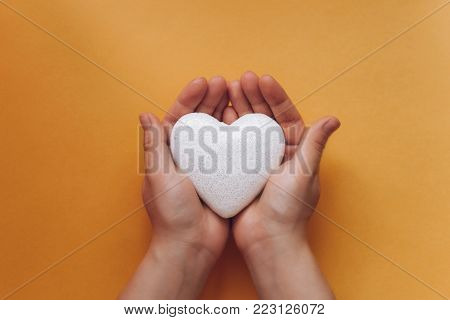 The girl is holding a symbol in the form of a heart