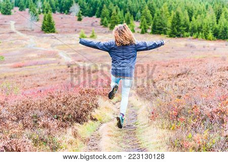 Young athletic, fit, free happy woman running jogging jumping in autumn, fall season meadow field path hike in mid-air