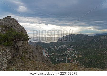 View from the top of Sokol mountain to the coastal resort town of Novy Svet, Crimea. Overcast rainy day.