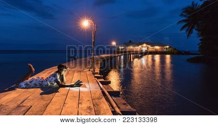Woman reading book at dusk, using forehead light, on a wooden warf, Hatta island, Maluku, Indonesia