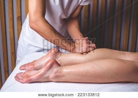 Hands of the masseur make a foot massage lying on the couch. The hands of a man do a foot massage in the massage salon. Legs lie on a white couch against the background of wooden walls.