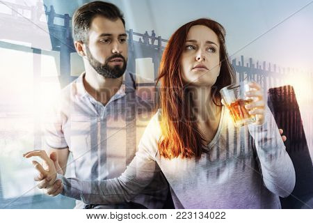 Stop it. Tired depressed young woman drinking alcohol and turning from her caring kind boyfriend while rejecting to listen to him