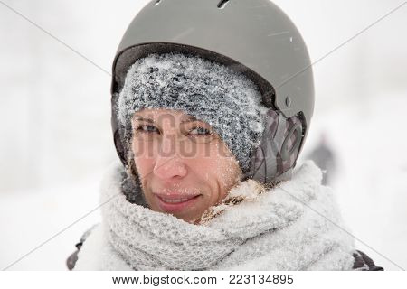 Smiling face of woman, wet snowy skin, cold winter outdoor, snow storm