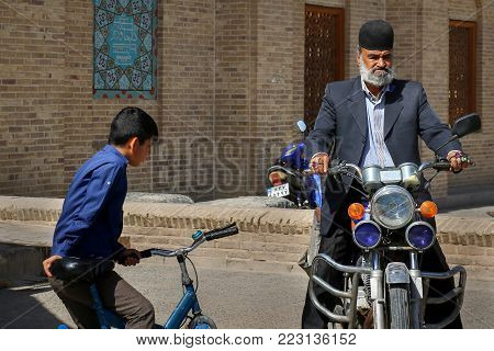 Iran, Persia, Yazd - September 21, 2016: A picturesque local elderly man in a traditional headdress and colorful rings is riding a motorcycle in the old town.