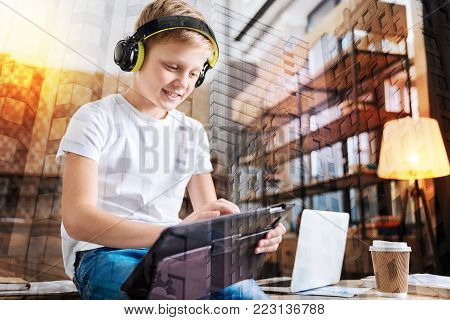 Wonderful device. Progressive smiling boy sitting on the table and feeling happy while listening to music in big headphones and playing on his new amazing tablet